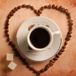 Heart from coffee beans around cup on old paper. top view — Foto de Stock