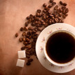 Cup of freshly brewed black coffee. top view. focus on beans - Stock Photo