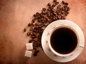 Cup of freshly brewed black coffee. top view. focus on beans — Stock Photo