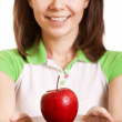 Young happy smiling woman give red apple on plate. Focus on appl - Stock Photo