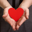 Red paper heart on the hands — Stock Photo