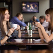 Stock Photo: Two girlfriens talking in cafe