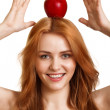 Young happy smiling woman with red apple on head isolated - Stock Photo