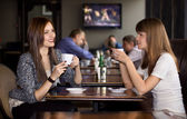 Two girlfriens talking in cafe — Stock Photo