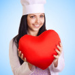 Female doctor holding heart on blue background - ストック写真