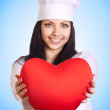 Stock Photo: Female doctor holding heart on blue background