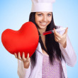 Stok fotoğraf: Happy female doctor inject syringe into red heart on blue