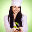 Portrait of smiling woman in white uniform holding plant in her — Stock fotografie