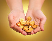 Hands with gold coins on yellow background — Stock Photo