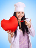 Happy female doctor inject a syringe into the red heart on blue — Stock Photo