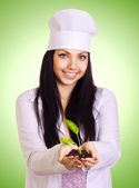 Portrait of smiling woman in white uniform holding plant in her — Stockfoto