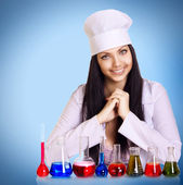 Young scientist at the table with test tubes on blue background — Stock Photo