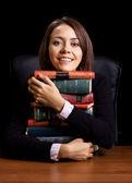 Jonge vrouw met vele boeken bij de receptie op zwarte achtergrond — Stockfoto