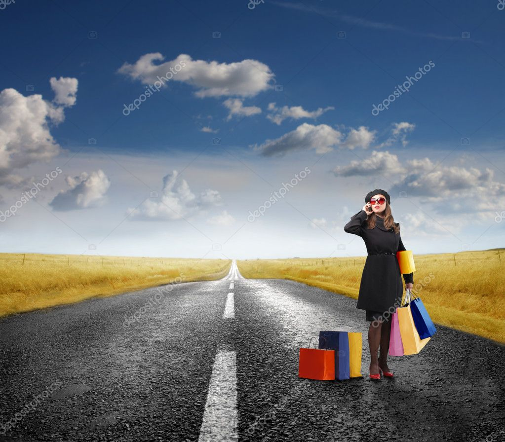 Elegant woman carrying some shopping bags while talking to telephone on a countryside road  Stock Photo #4011829