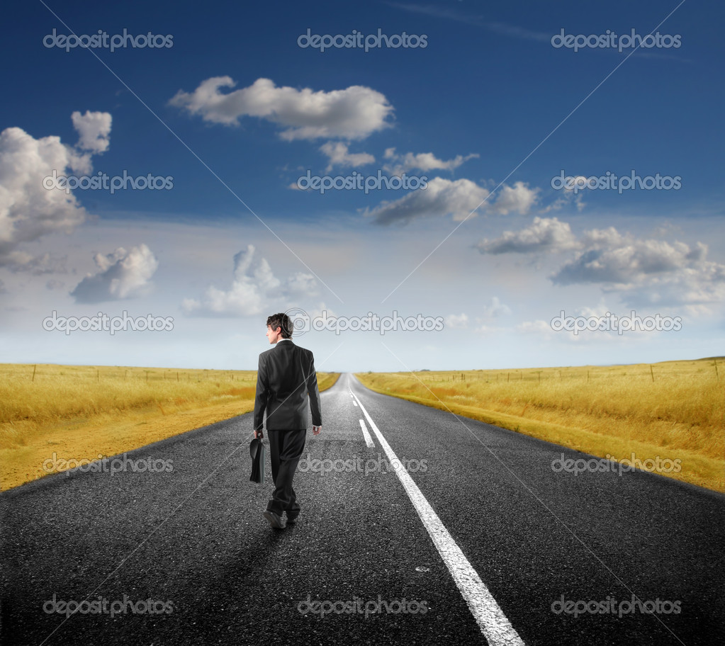 Businessman walking on a countryside road — Stock Photo #4012273