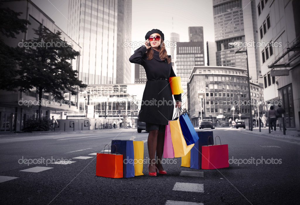 Elegant woman with many shopping bags talking to telephone on a city street — Stock Photo #4012424