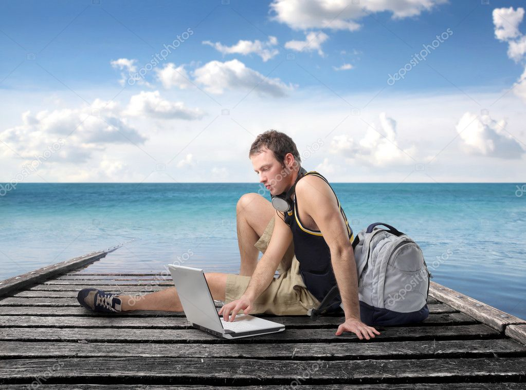 Young man sitting on a wharf and using a laptop — Zdjęcie stockowe #4012566