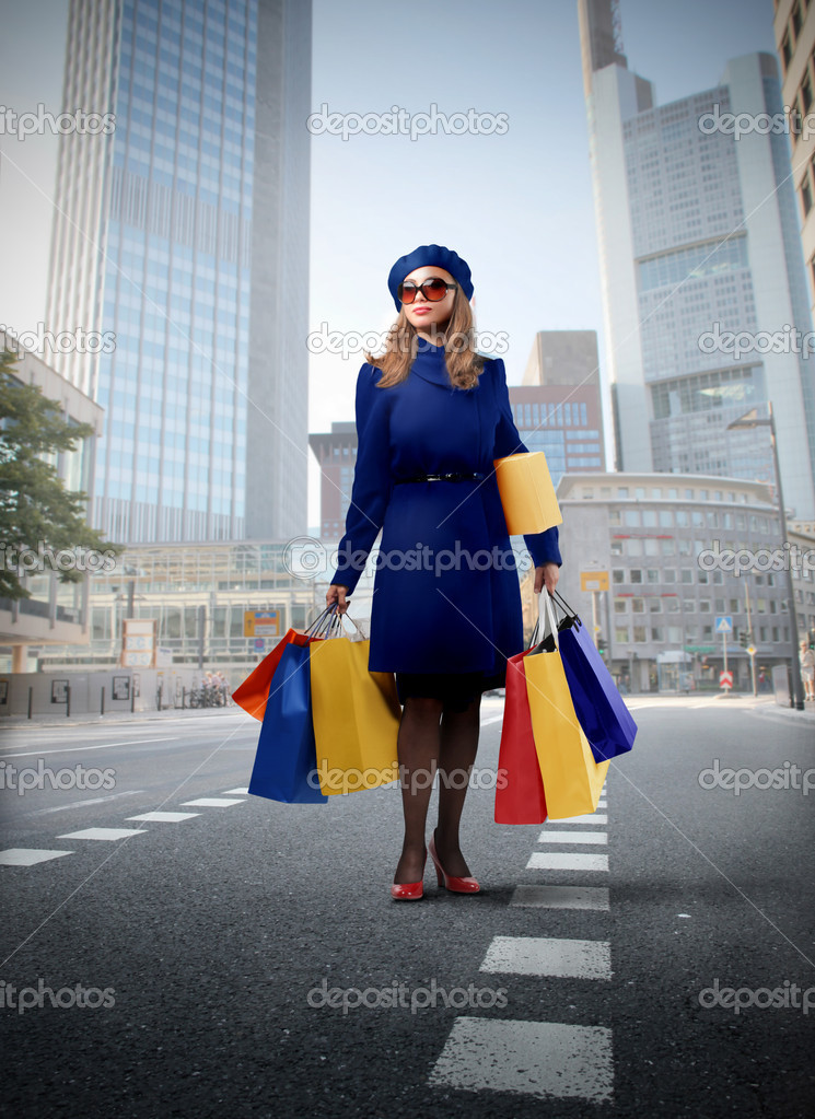 Elegant woman carrying many shopping bags on a city street — Stock Photo #4012654