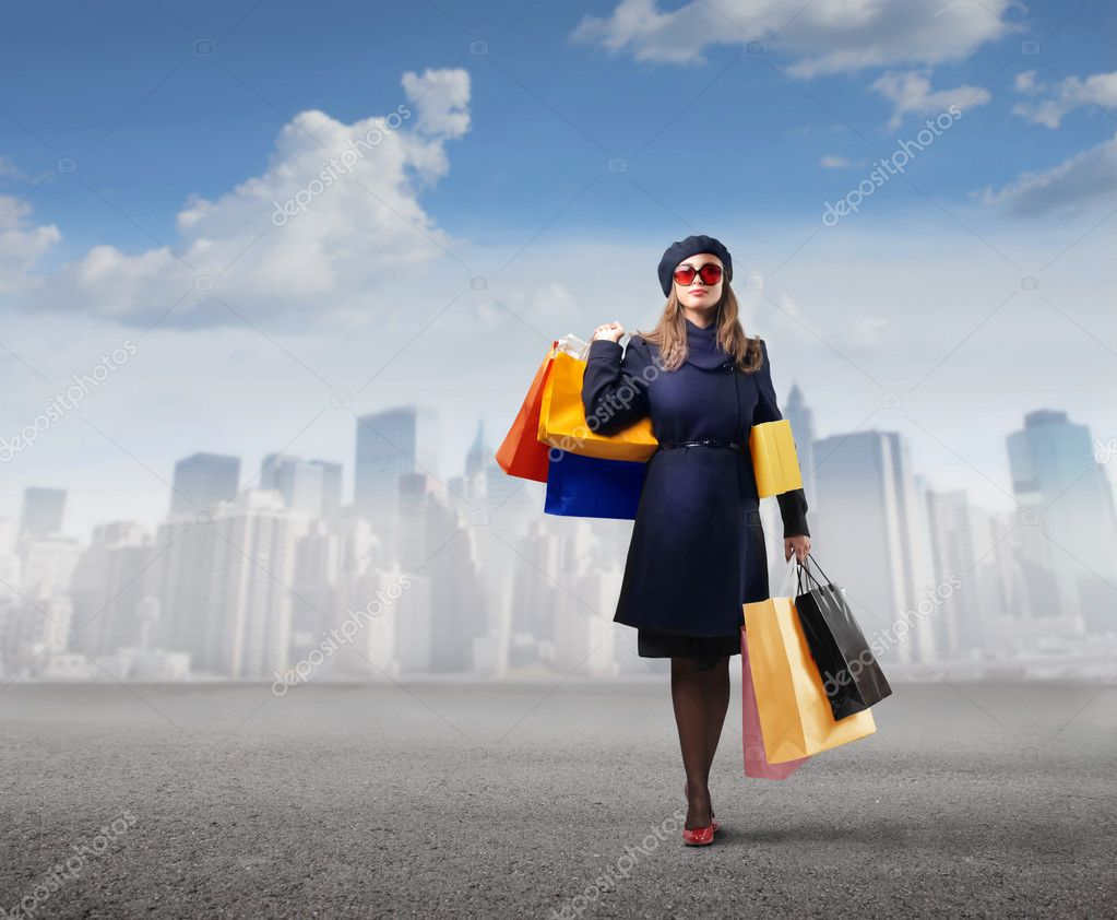 Elegant woman carrying many shopping bags with cityscape on the background — Stock Photo #4012680