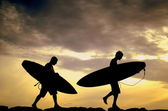 Two Surfers Carrying Their Boards Home At Sunset — Stock Photo