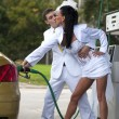 Bride and groom kissing at fuel station — Stock Photo