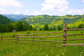 Wooden fence in green mountains — Stock Photo