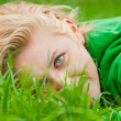 Young blonde lying in a grass — Stock Photo