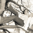 Girl sits on tree branches — Stock Photo