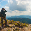 Hiker stands on a peak — Stock Photo