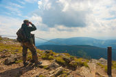 Hiker stands on a peak — Stockfoto