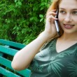 Stock Photo: Beautiful girl talking at mobilephone on park bench