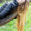 Beautiful girl laughing, on a tree branch — Stock Photo