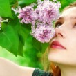 Young woman smelling lilac blossoms — Stock Photo