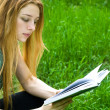 Royalty-Free Stock Photo: Young female student reading in park