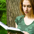 Beautiful female student reading in campus — Stock Photo