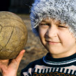 Needy boy with warn ball in his hand — Stock Photo