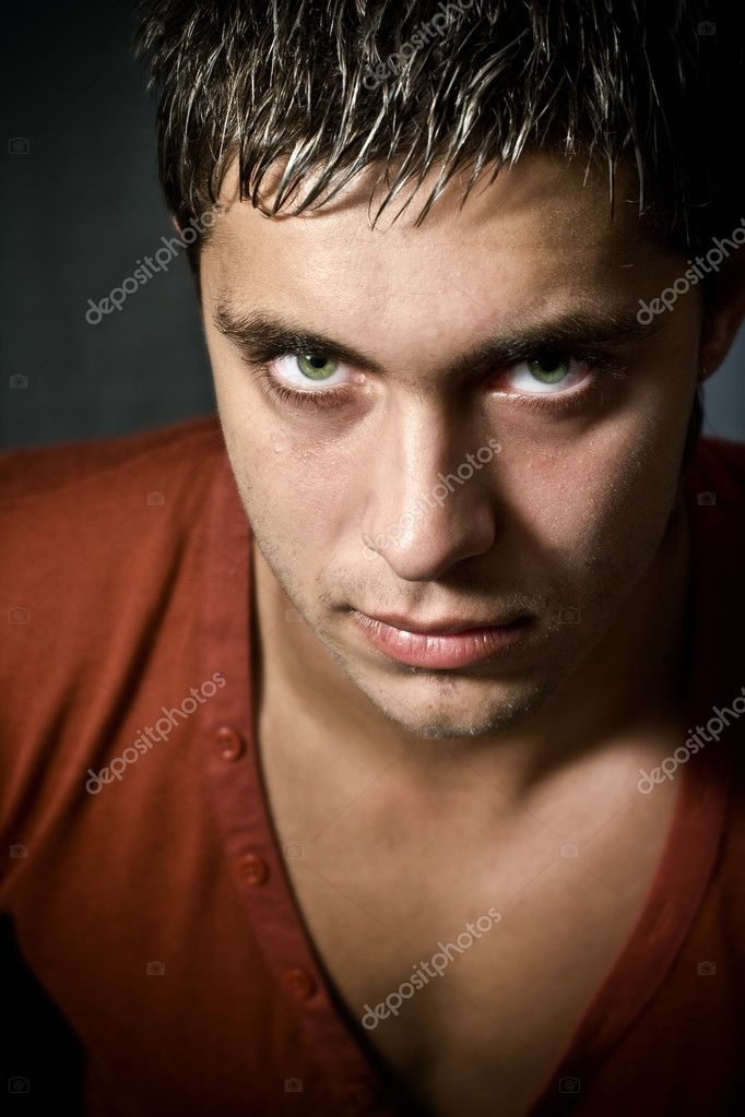 Low key portrait of intense looking guy with green eyes — Stock Photo #4941883