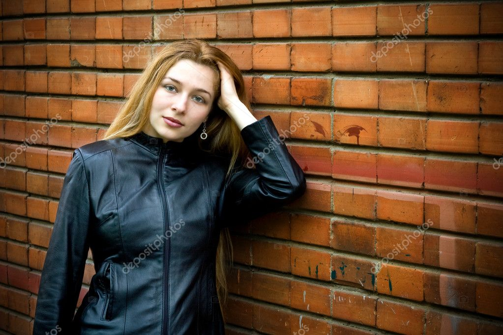 Beautiful blond girl standing in front of old brick wall — Stock Photo #4942445