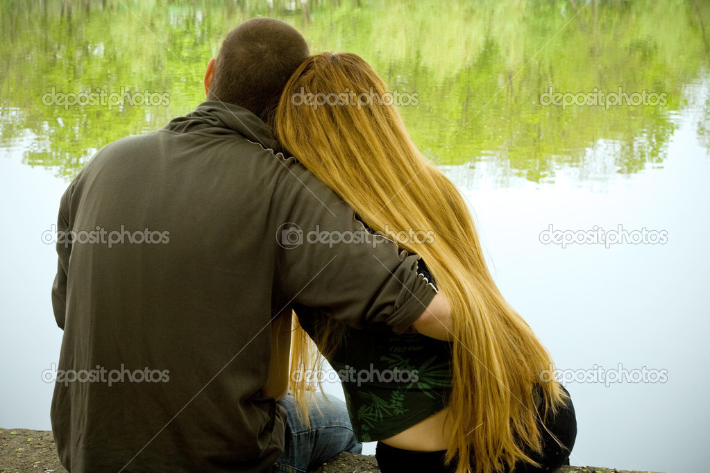 Lovers hugging and sitting on lakeside  Stock Photo #4942690