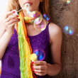 Woman blowing colorful soap bubbles - Stockfoto
