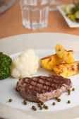 Juicy steak on a wooden table — Stock Photo