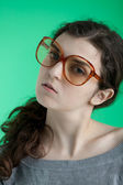 Girl with big glasses on a green background — Stock Photo