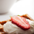 Fresh waffle with cream and a strawberry — Stock Photo