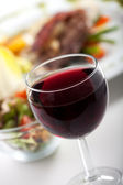 Glass of red wine and dinner — Stock Photo