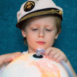 Cute dreaming child with the globe model — Stock Photo