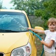 Stock Photo: Little boy washing yellow car.
