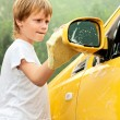 图库照片: Little boy washing yellow car.