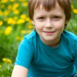 The boy in dandelions field. — Stock Photo