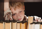 The boy at a bookcase gets the book. — Stock Photo