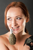 Closeup portrait of a young pretty female model holding grenade pin — Stock Photo